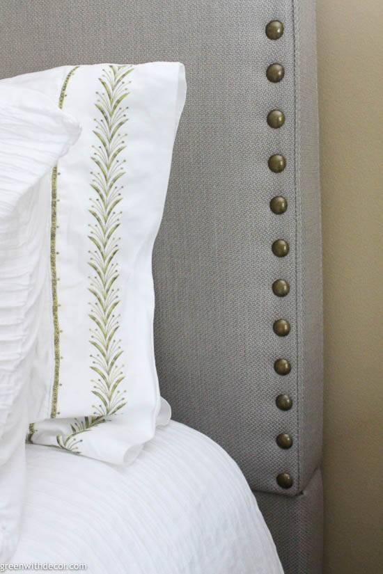 Gray upholstered headboard with white and green sheets