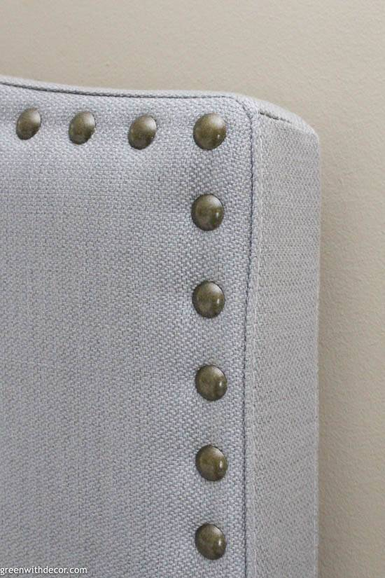 Gray upholstered headboard with gold nailheads
