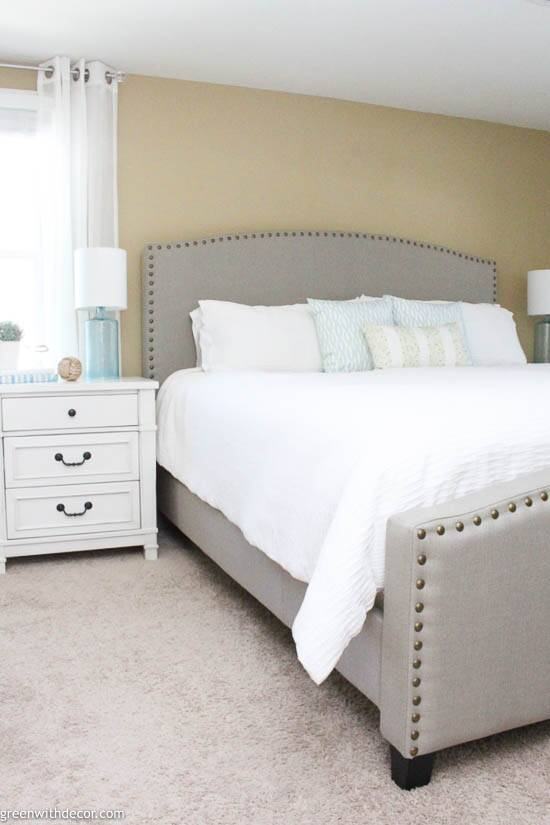 Coastal bedroom with gray headboard and white bedding