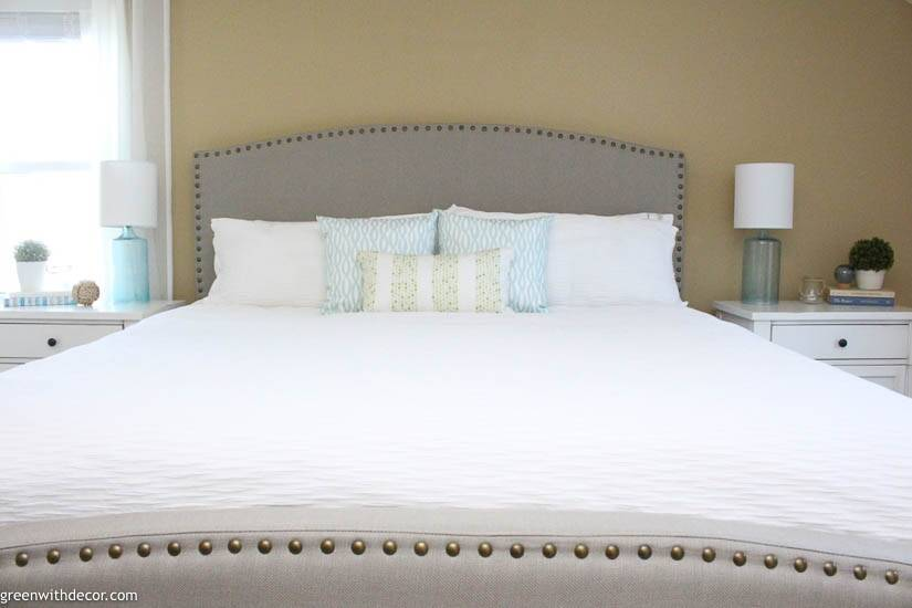 Coastal bedroom with gray upholstered headboard