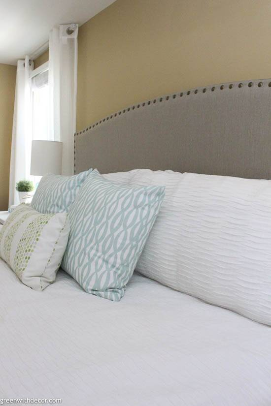 Coastal bedroom with upholstered headboard and pillows