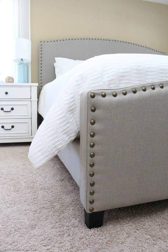 Coastal bedroom with gray upholstered headboard and whtie nightstand