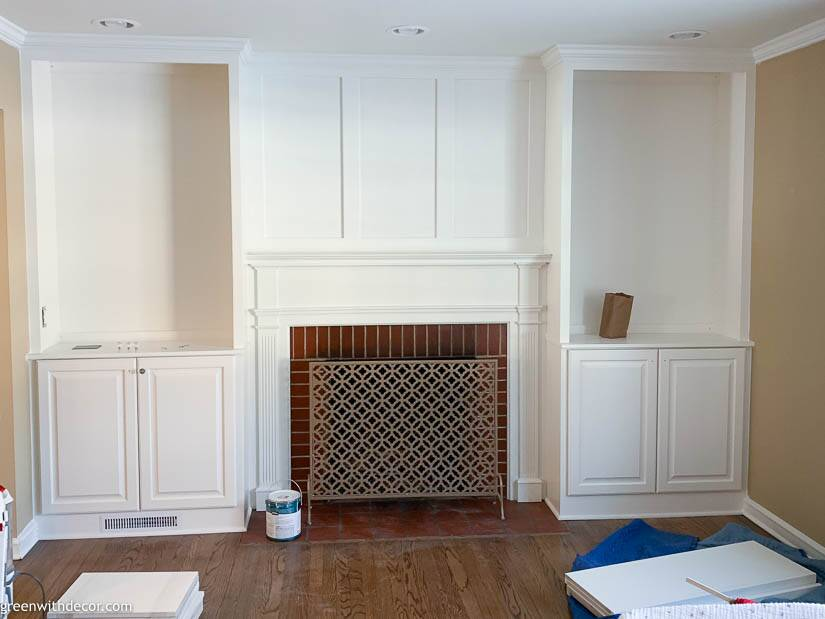 White built-in bookshelves with board and batten above the fireplace