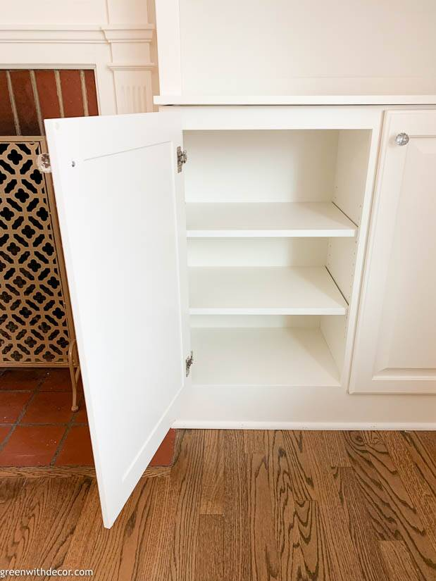 Bottom cabinets of white built-in bookshelves around non-recessed fireplace