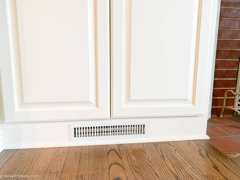 Heating vent at bottom of white built-in bookshelves around a fireplace