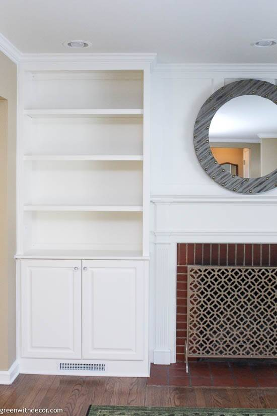 White built-in bookshelves around a brick fireplace