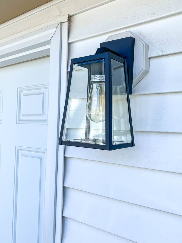 Dark outdoor light with white siding