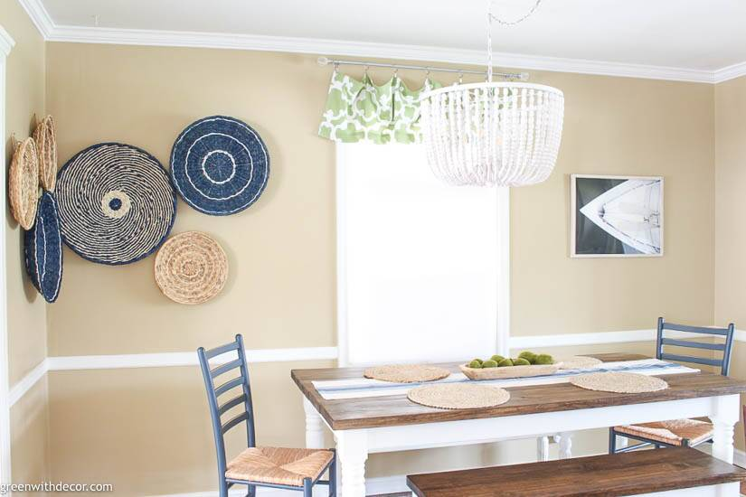 Boho coastal dining room with a seagrass basket gallery wall and beaded chandelier