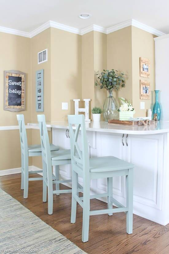 A white and tan coastal kitchen with painted barstools