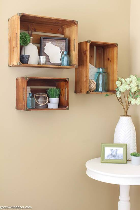 3 wood crate shelves on a tan wall near a white round table