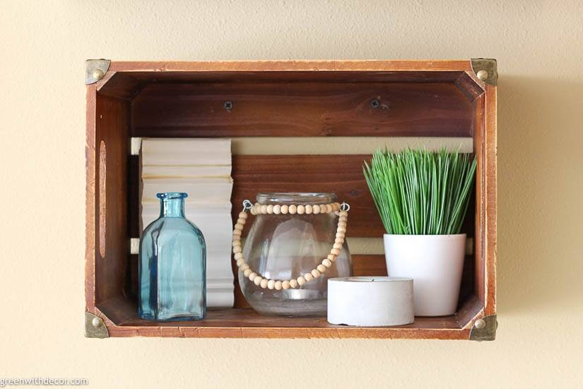 A wood crate shelf with an aqua glass bottle, faux grass and candle holders