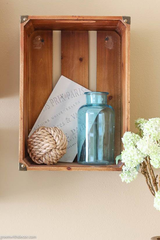A wood crate shelf with an aqua glass vase and rope sphere