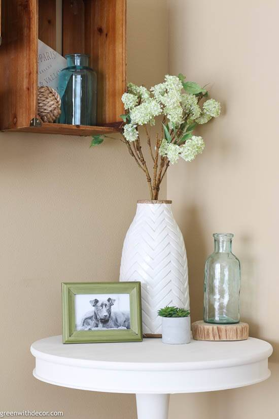 A white and wood vase with green hydrangeas on a white table