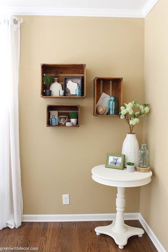 Wood crate shelves on a tan wall with white curtains