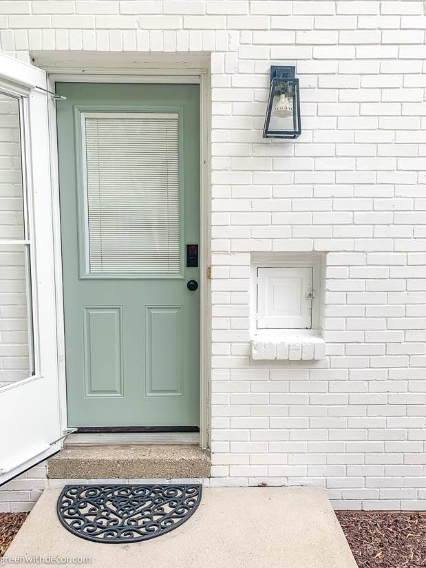 White brick house with blue door and black light fixture