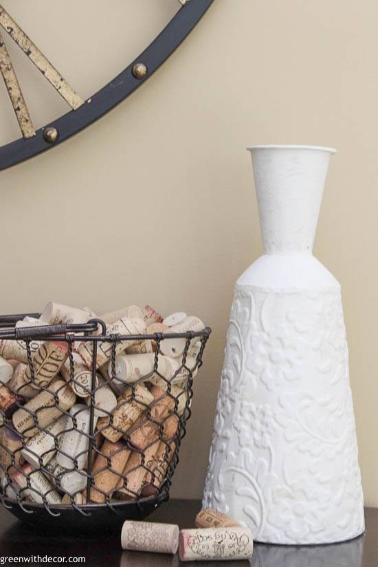 A painted vase next to a basket of wine corks