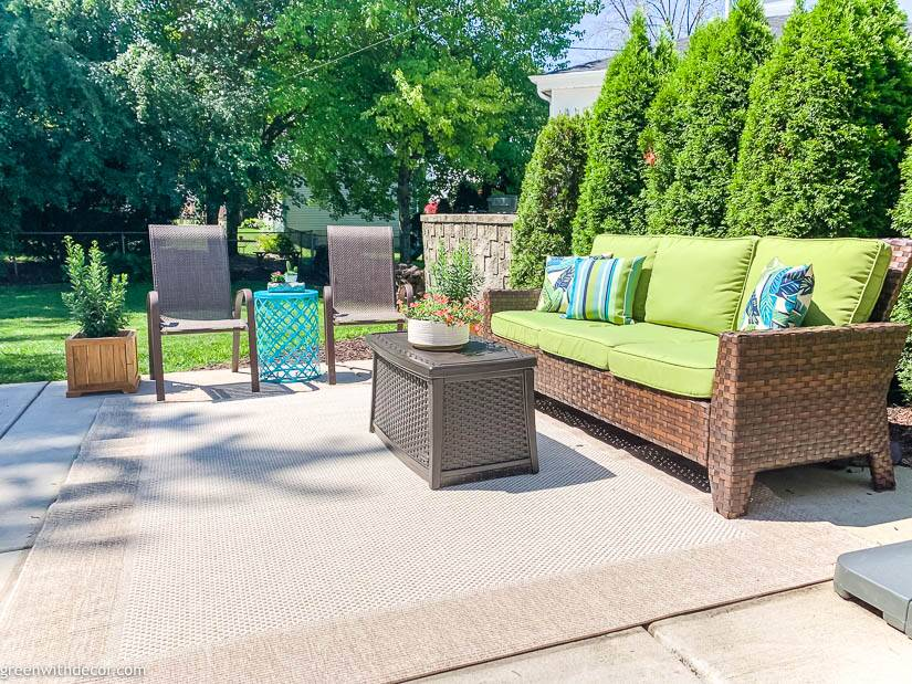 Summer patio with tan area rug and green outdoor couch