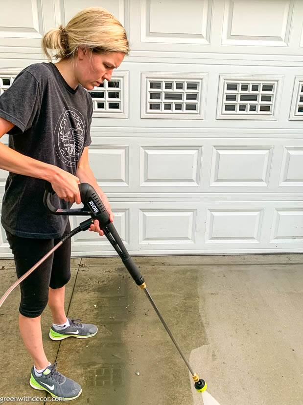 A girl pressure washing a concrete driveaway