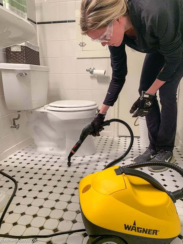 A girl using a stem cleaner to clean a bathroom floor