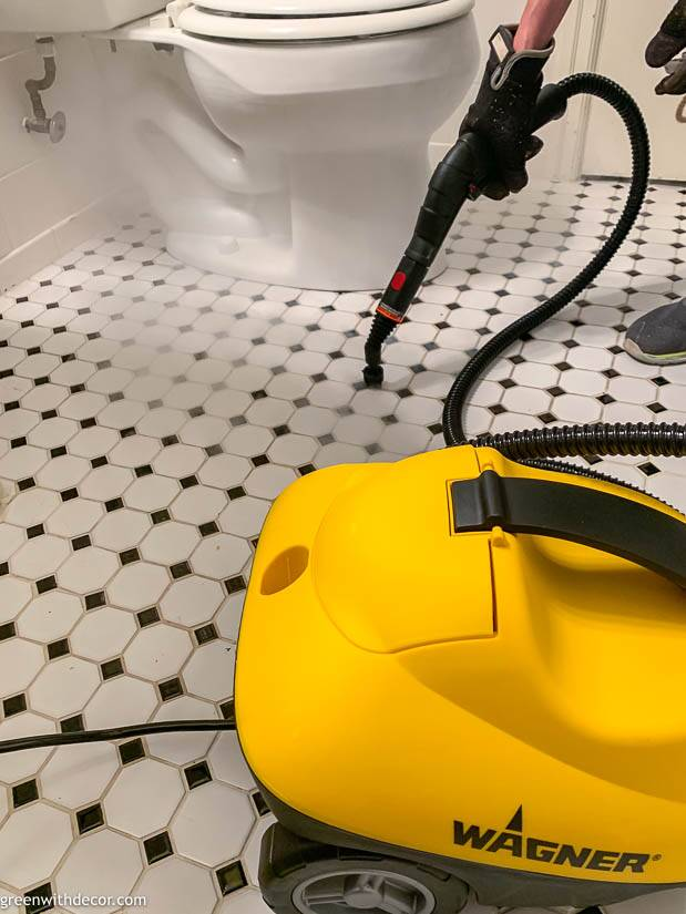 A steam cleaner cleaning a white and black bathroom tile floor