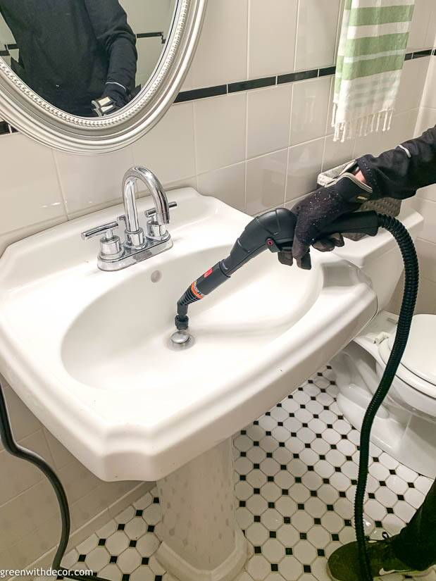 Steam cleaner being used to clean a white bathroom sink