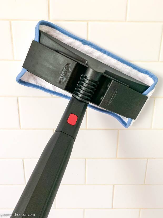 A steam cleaner cleaning subway tile