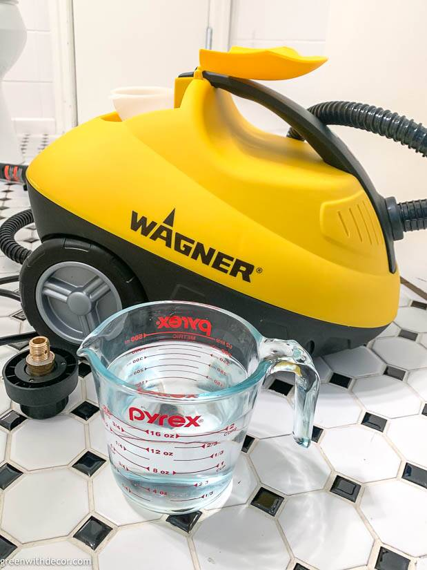 A measuring cup with water in front of a Wagner steam cleaner
