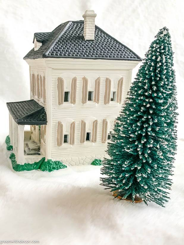 White painted Christmas village house with tan shutters, black roof and white chimneys