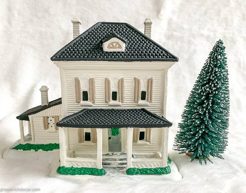 White painted Christmas village house with black roof, white chimneys and tan shutters
