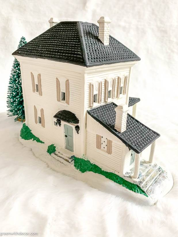 White painted Christmas village house with black roof, blue door and green bushes