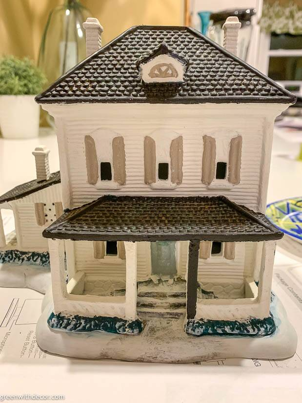 White painted Christmas village house with white and black porch posts