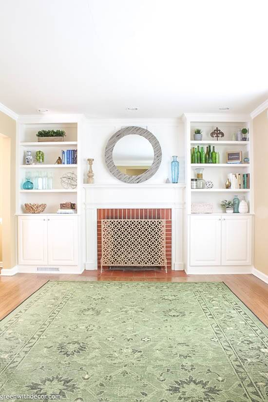 White bookshelves decorated with costal pieces around a red brick fireplace