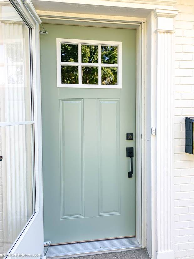 Blue front door with white window and black hardware on white brick house