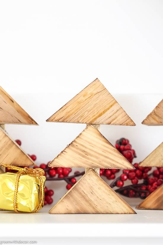 DIY burned wood Christmas trees by red berries and gold presents