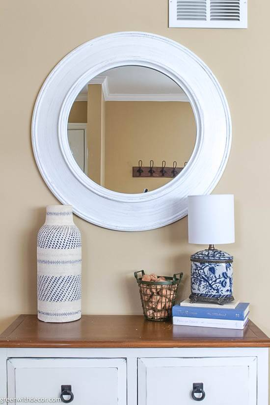 Small coastal foyer with white round mirror
