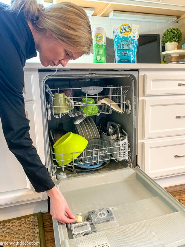 Girl loading  the dishwasher with detergent