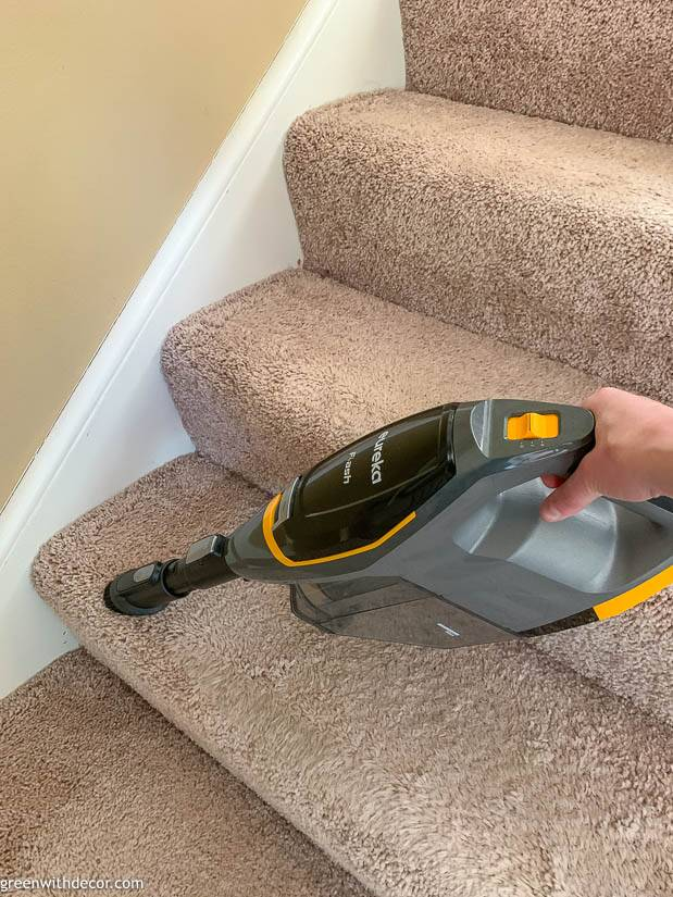 Vacuuming tan carpeted stairs