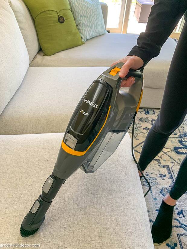 Vacuuming a gray couch