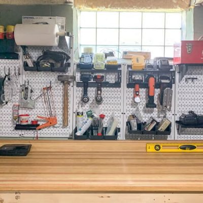 White pegboard tool organization near glass block window