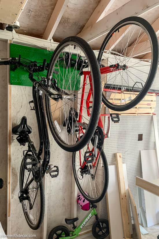 Green pegboard with hooks for hanging bikes