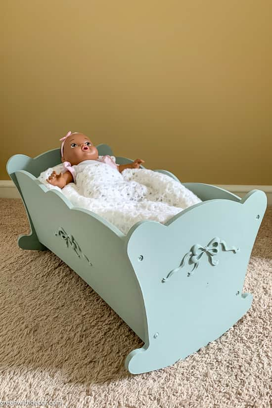 Blue painted doll cradle with doll