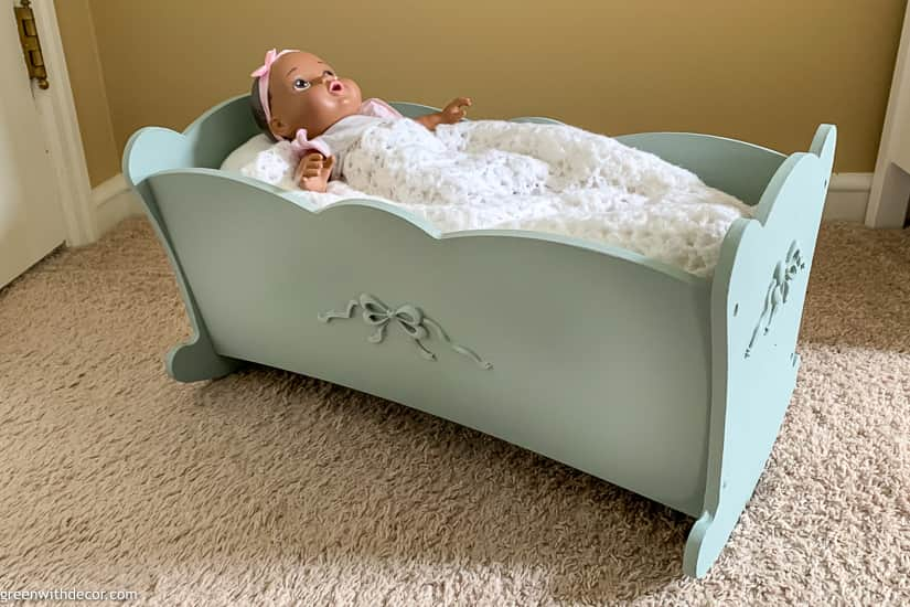 Painted blue doll cradle near tan wall